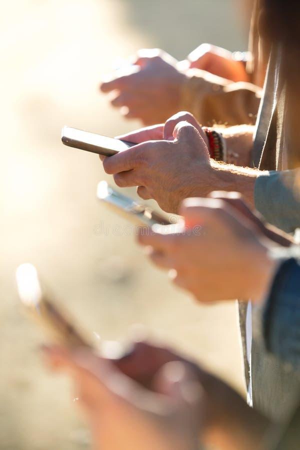 Молодая группа в составе друзья беседуя с их смартфонами в улице стоковые фотографии rf