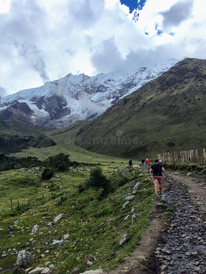 Молодая группа в составе международные hikers, приведенная их местным проводником Inca, проводит горы Анд на следе Salkantay стоковое фото