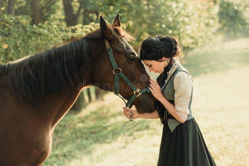 Молодая дама в винтажном платье, с нежностью и с привязанностью обнимает ее лошадь Старый, собранный стиль причёсок, a стоковое изображение