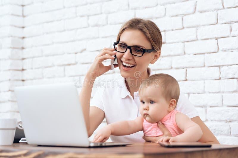 Молодая дама дела пробует работать с меньшим младенцем стоковое фото rf