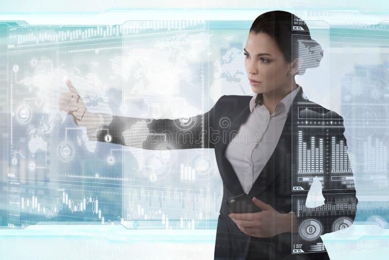 Молодая дама дела работает с виртуальным графическим интерфейсом в футуристическом офисе стоковая фотография rf