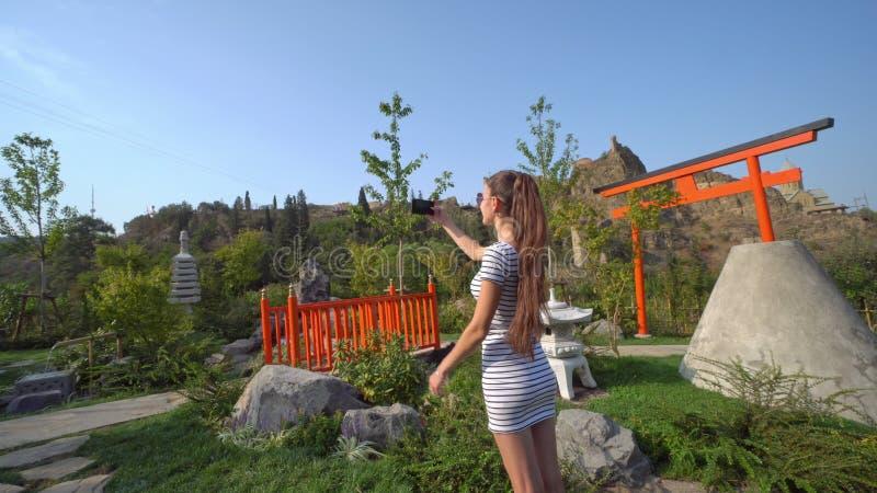 Молодая дама принимая фото снаружи стоковые фото