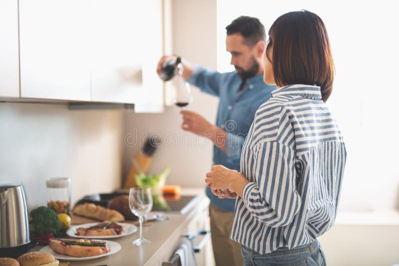 Молодая дама смотря парня пока он лить вино в стекло стоковые изображения rf