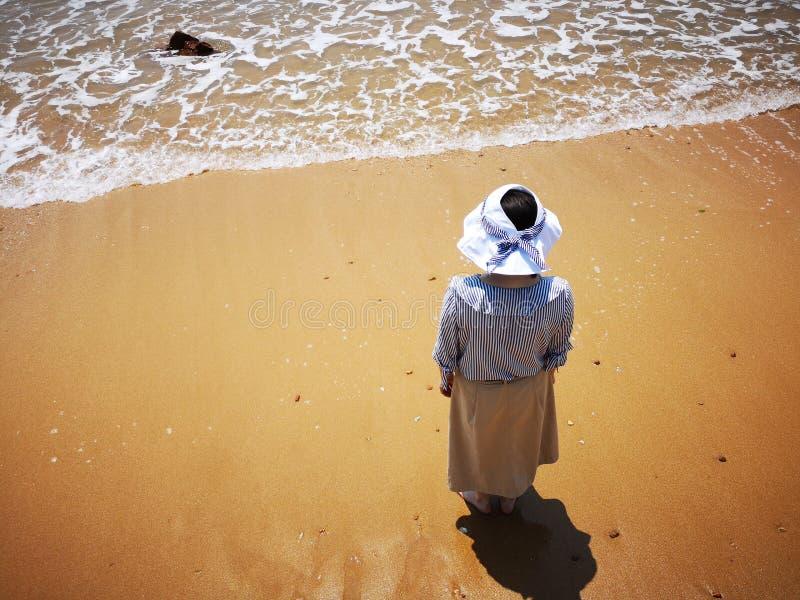 Молодая дама стоя на пляже стоковые фото