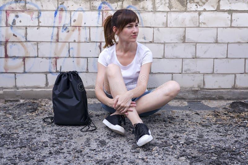 Молодая девушка битника сидит на кирпичной стене с рюкзаком drawstring стоковое фото rf