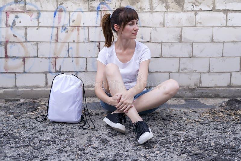 Молодая девушка битника сидит на кирпичной стене с рюкзаком drawstring стоковые изображения rf