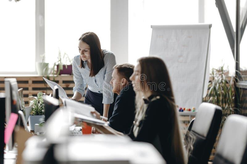 Молодая девушка брюнета одетая в одеждах стиля офиса сидит на столе с коллегами и держит тетрадь стоковые изображения