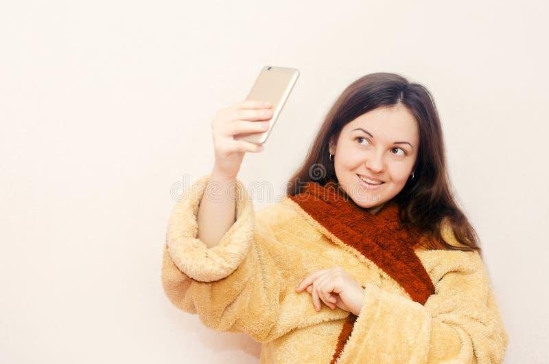 Молодая девушка брюнет в купальном халате делает selfie стоковые изображения rf