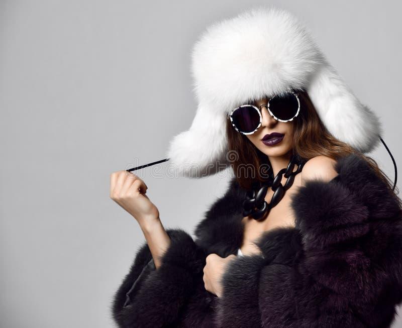 Молодая девушка моды в меховой шыбе и белой шляпе в современных круглых солнечных очках на темноте стоковое фото rf