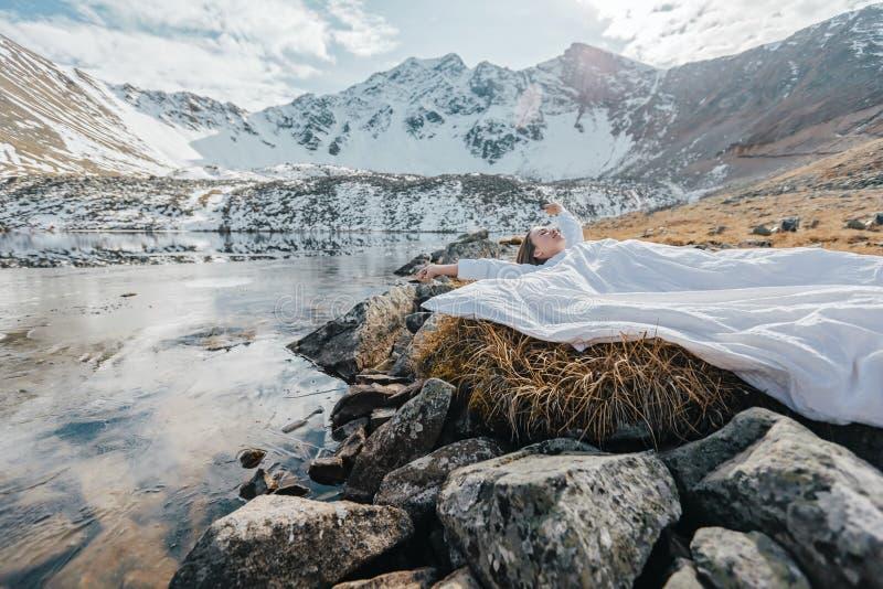 Молодая девушка отдыхает в комфортной постели в дикой природе с видом на красивый пейзаж зимой стоковые фото