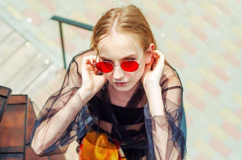 Молодая девушка подростка в красных солнечных очках Взгляд сверху, смотря вверх стоковые фотографии rf