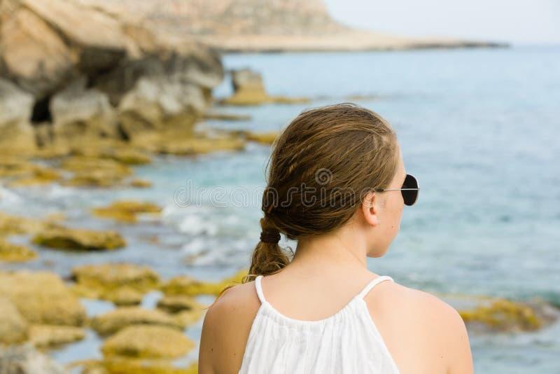 Молодая девушка подростка в солнечных очках в белой верхней части, outdoors, береге моря Кипра стоковые изображения