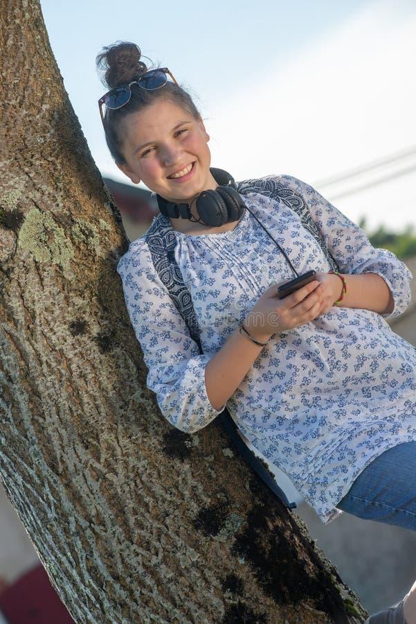 Молодая девушка подростка ждать школьный автобус и используя ее смартфон стоковые изображения rf