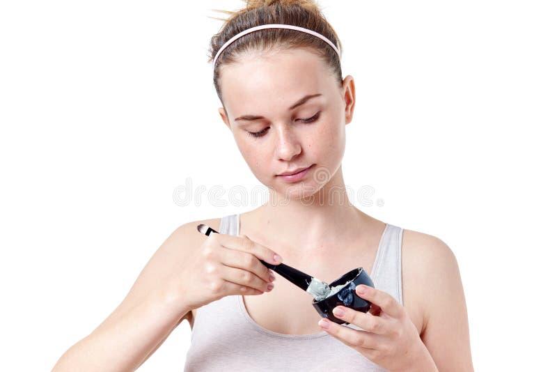 Молодая девушка подростка прикладывая лицевую маску используя щетку, на белой предпосылке стоковое изображение rf