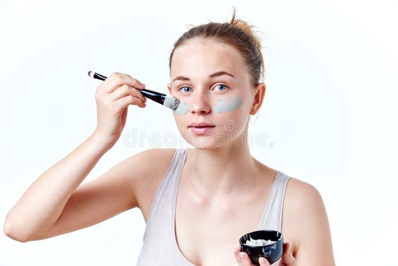 Молодая девушка подростка прикладывая лицевую маску используя щетку, на белой предпосылке стоковые фото