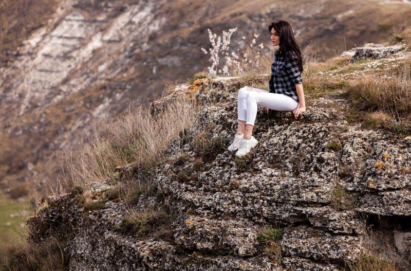 Молодая девушка путешественника сидит на верхней части долины Маленькая девочка любит дикую жизнь, перемещение, свободу Женщина п стоковые фотографии rf