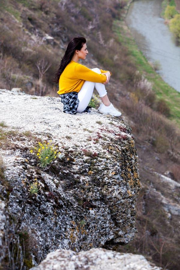 Молодая девушка путешественника сидит на верхней части долины Маленькая девочка любит дикую жизнь, перемещение, свободу Женщина п стоковые фото