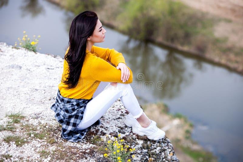Молодая девушка путешественника сидит на верхней части долины Маленькая девочка любит дикую жизнь, перемещение, свободу стоковое изображение rf