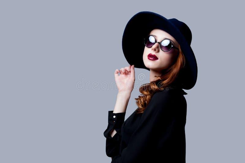 Молодая девушка redhead в темном стиле в солнечных очках стоковая фотография