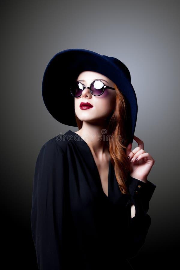 Молодая девушка redhead в темном стиле в солнечных очках стоковые изображения rf