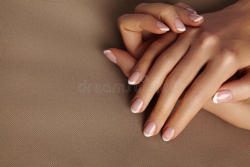 Молодая женская ладонь Красивый маникюр очарования французский тип сделайте продукты маникюра вверх Позаботьте о руках и ногтях,  стоковые изображения