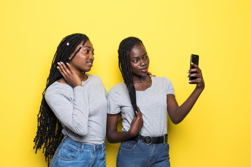Молодая женщина африканца красоты делает видео- звонок или selfie на телефоне изолированном на желтой предпосылке стоковые фотографии rf