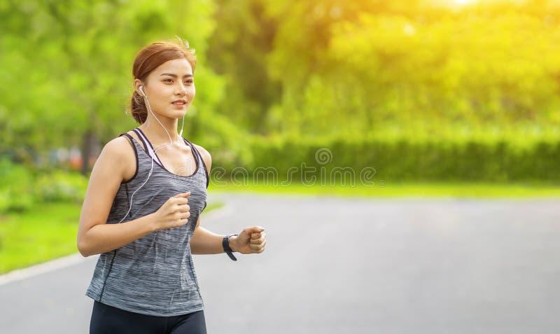 Молодая женщина бежать на дороге в утре, молодой бегун спорта фитнеса спортсменки фитнеса бежать на тропическом следе парка Peo стоковая фотография