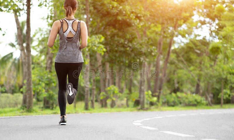 Молодая женщина бежать на дороге в утре, молодой бегун спорта фитнеса спортсменки фитнеса бежать на тропическом следе парка Peo стоковые фотографии rf