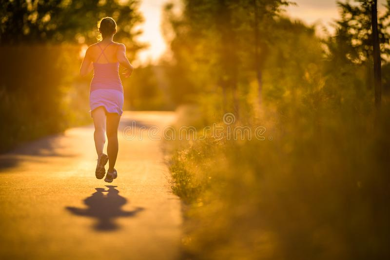Молодая женщина бежать outdoors на evenis прекрасных солнечных лета стоковое изображение rf