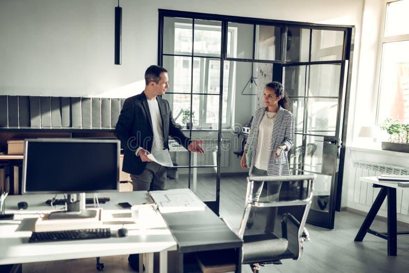 Молодая женщина бизнесмена приглашая, который нужно сидеть вниз перед интервью стоковые изображения rf