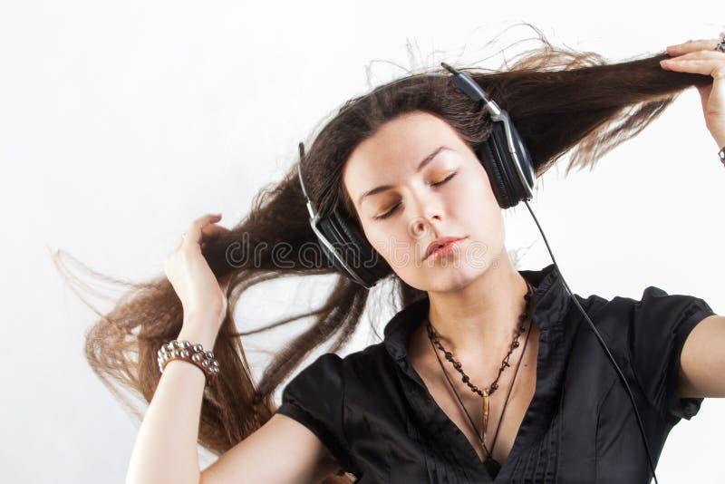 Молодая женщина брюнета в больших наушниках слушая музыку и имея потеху стоковые фотографии rf