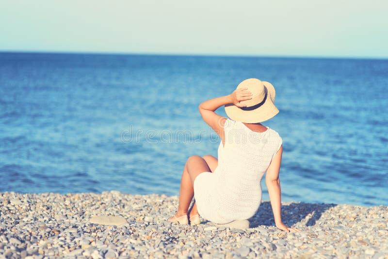 Молодая женщина брюнета в посадочных местах платья лета белых на пляже и смотреть к морю Кавказская девушка ослабляя и наслаждаяс стоковая фотография rf