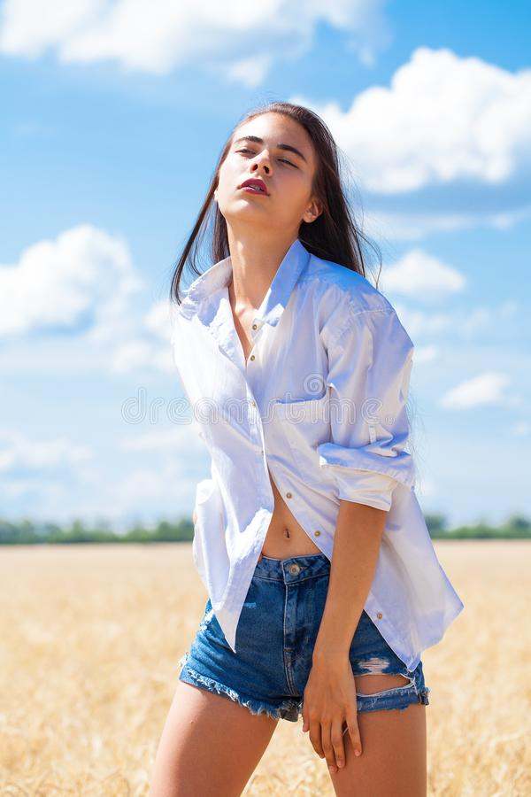 Молодая женщина брюнета в шортах белой рубашки и голубых джинсов стоковая фотография rf
