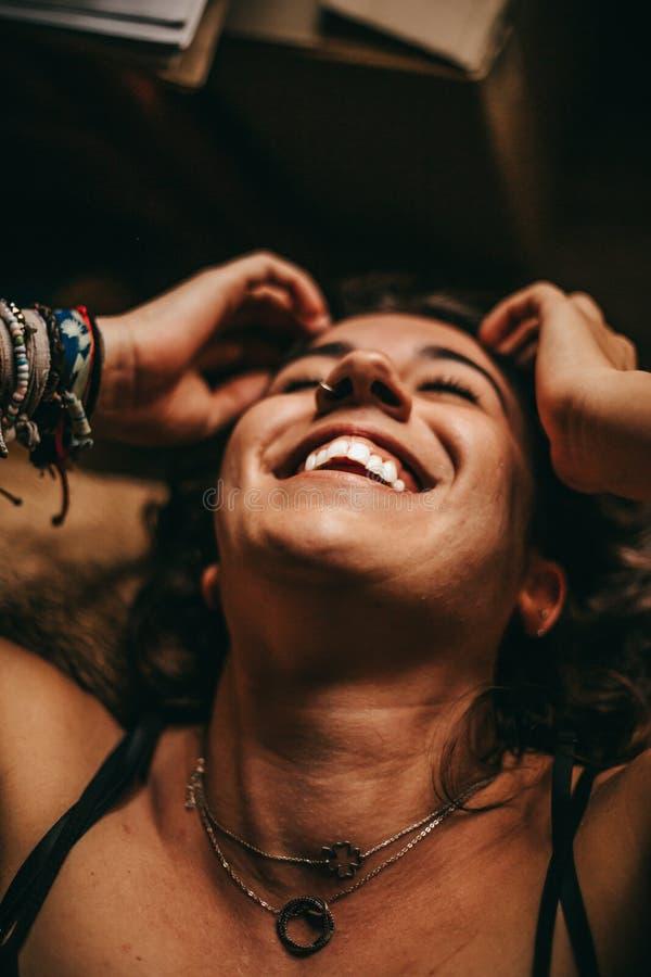 Молодая женщина брюнета лежа и смеясь стоковое изображение