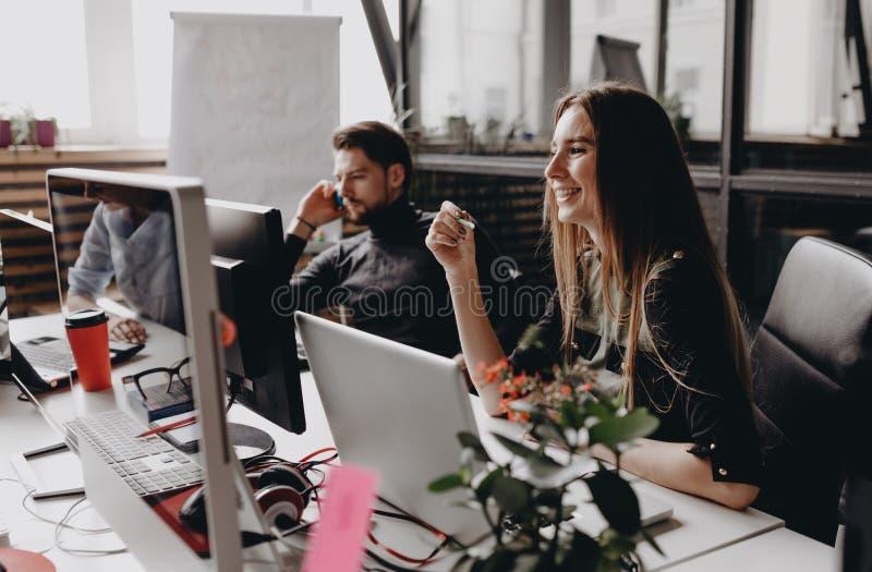 Молодая женщина брюнета одетая в одеждах стиля офиса работает на компьютере сидя на столе с коллегами стоковое фото