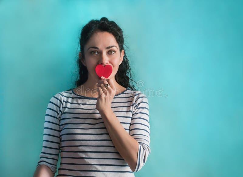 Молодая женщина брюнета с красным сердцем и striped рубашкой стоковые изображения
