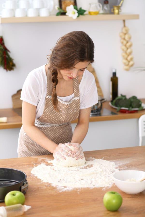 Молодая женщина брюнет варя пиццу или handmade макаронные изделия в кухне Домохозяйка подготавливая тесто на деревянном столе die стоковое изображение