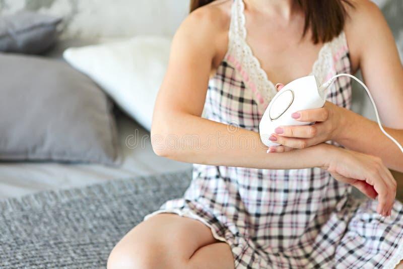 Молодая женщина брюнет держа прибор для фото-epilation сидит стоковое изображение