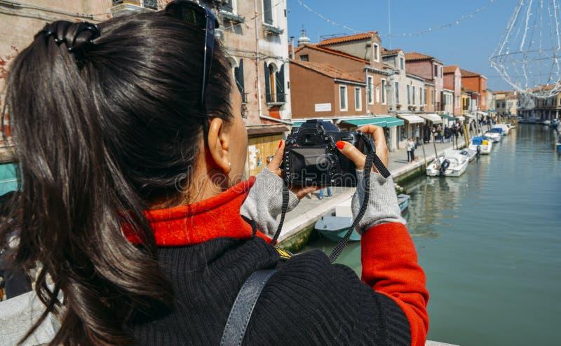 Молодая женщина брюнет фотографирует красочный канал в Murano с камерой DSLR стоковое фото