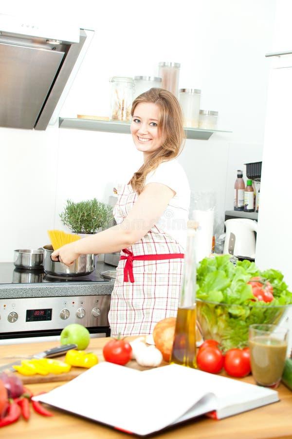 Молодая женщина варя в кухне Здоровая еда - соль овоща стоковое фото