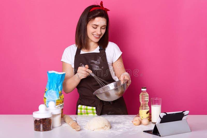 Молодая женщина варя в кухне, смешивая продуктах с венчиком, подготавливающ на праздник пасхи, находящся в хорошем настроении, но стоковое изображение