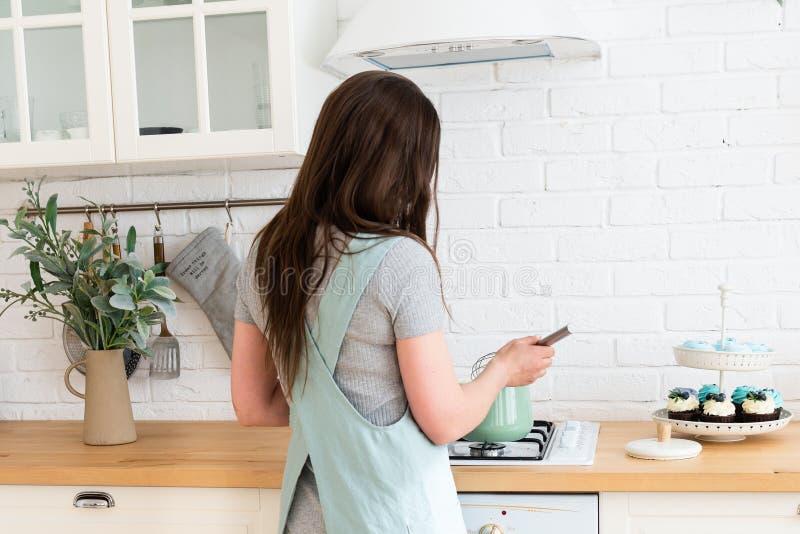 Молодая женщина варя в кухне E o Варить дома Подготовка еды confectioner Домодельный стоковые фотографии rf