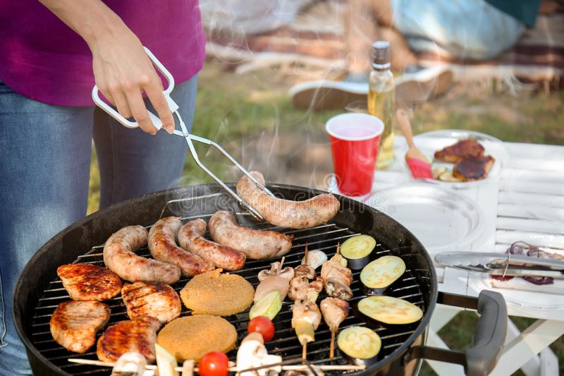 Молодая женщина варя мясо и овощи на гриле барбекю outdoors стоковая фотография