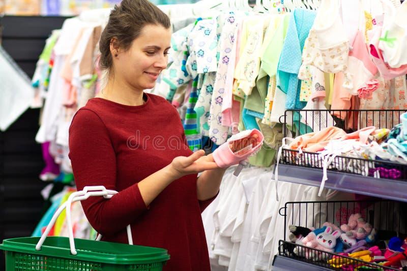Молодая женщина выбирает одежды для младенца стоковая фотография rf