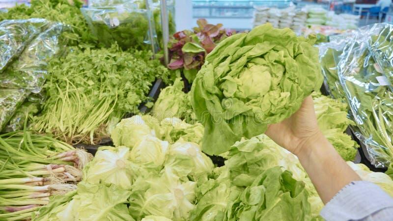 Молодая женщина выбирая зеленые овощи в гастрономе стоковые фото