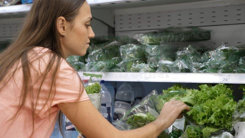 Молодая женщина выбирая свежий салат на отделе бакалеи на торговом центре стоковая фотография rf