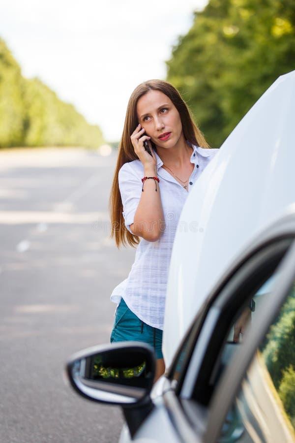 Молодая женщина вызывая помощь о тревогах с ее автомобилем стоковое изображение rf