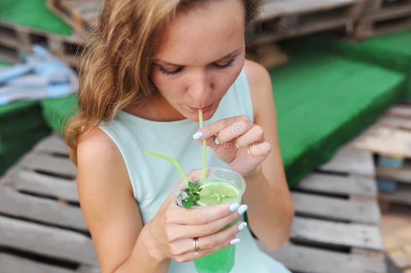 Молодая женщина выпивая с коктеилем известки и мяты с выпивая соломой в стекле стоковое изображение