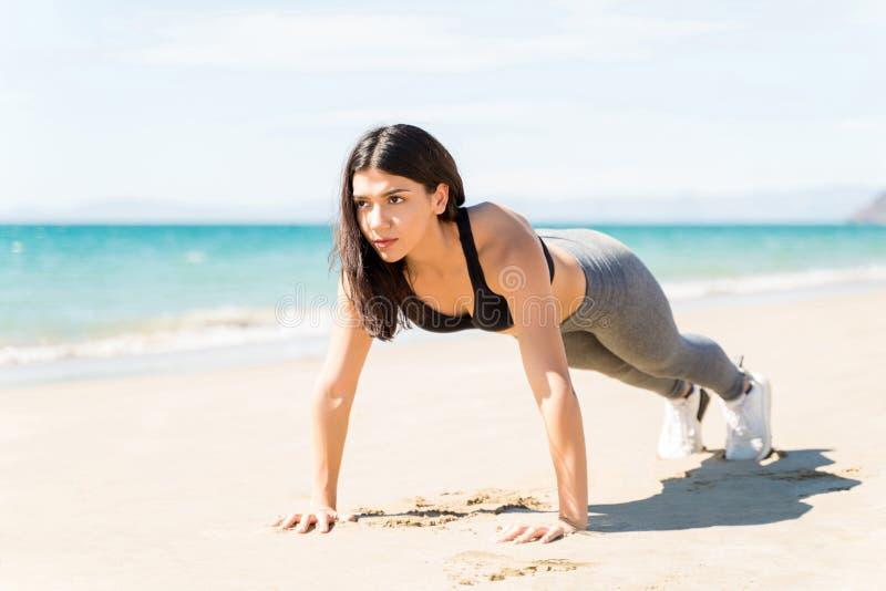 Молодая женщина, выполняющая планк на пляже стоковое фото rf