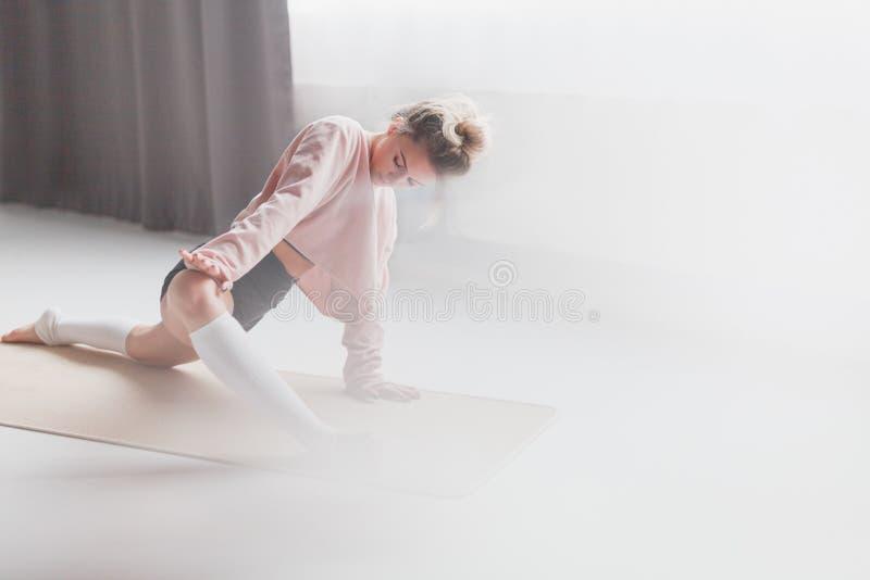 Молодая женщина выполняя выпад на колене стоковая фотография